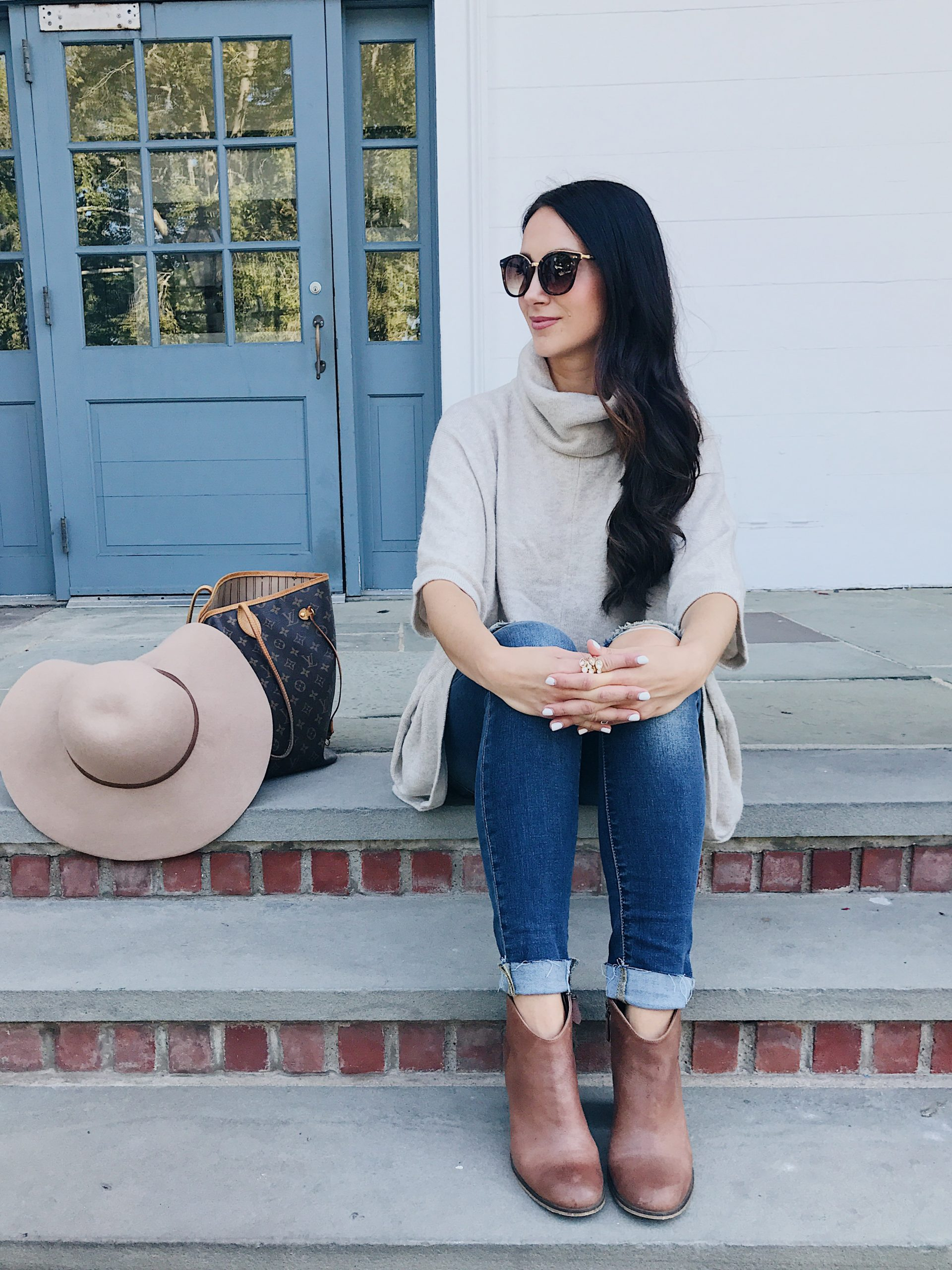 blogger Anna Monteiro of Blushing Rose Style blog wearing fall outfit poncho, brown ankle booties and oversized sunglasses.