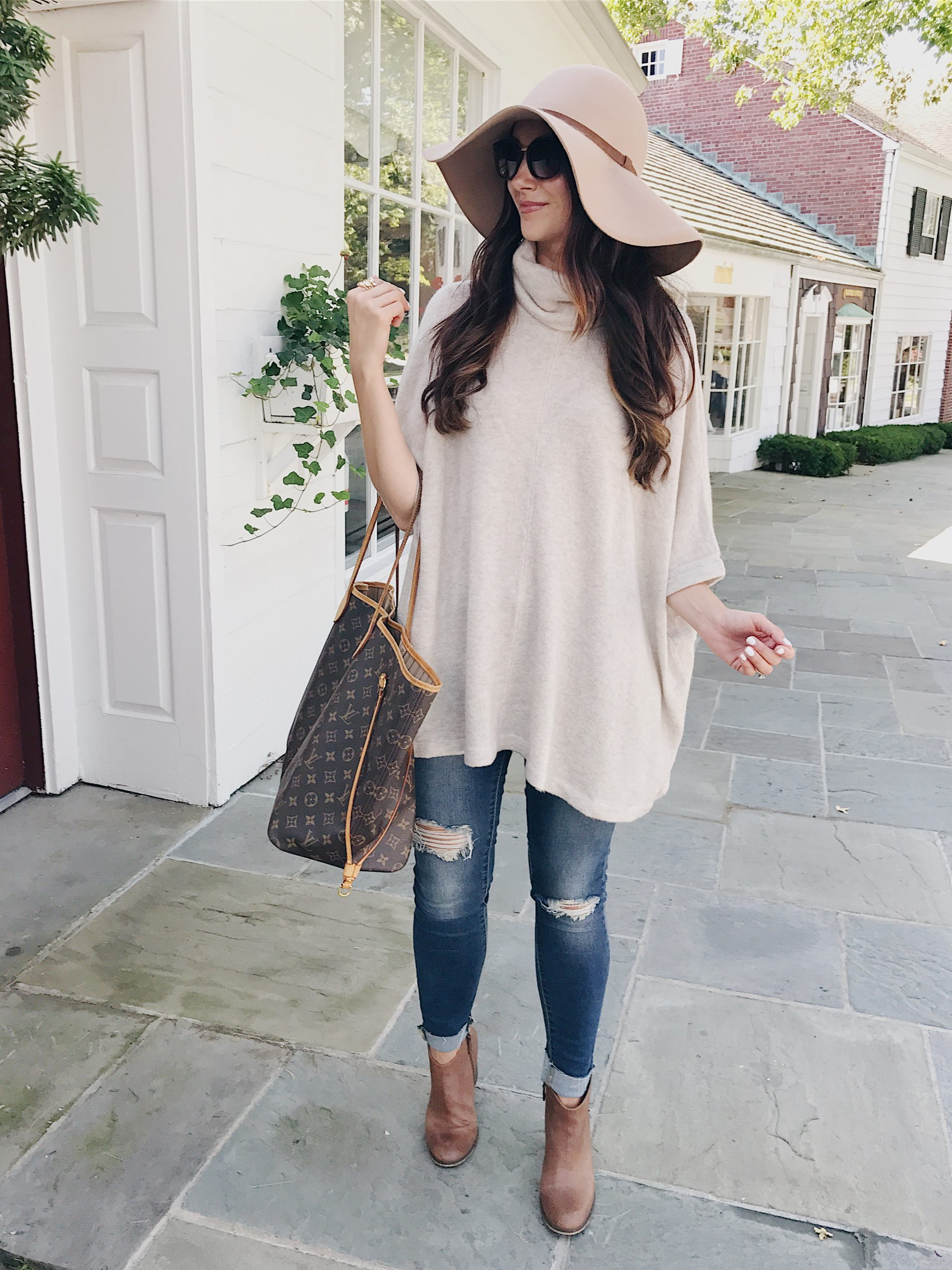 blogger Anna Monteiro of Blushing Rose Style wearing fall outfit floppy hat, brown booties and sweater poncho.