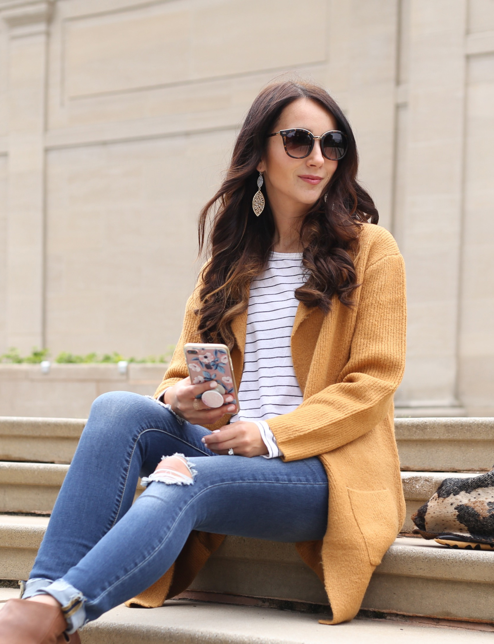 blogger Anna Monteiro wearing cozy fall sweaters with striped tee and leopard print scarf