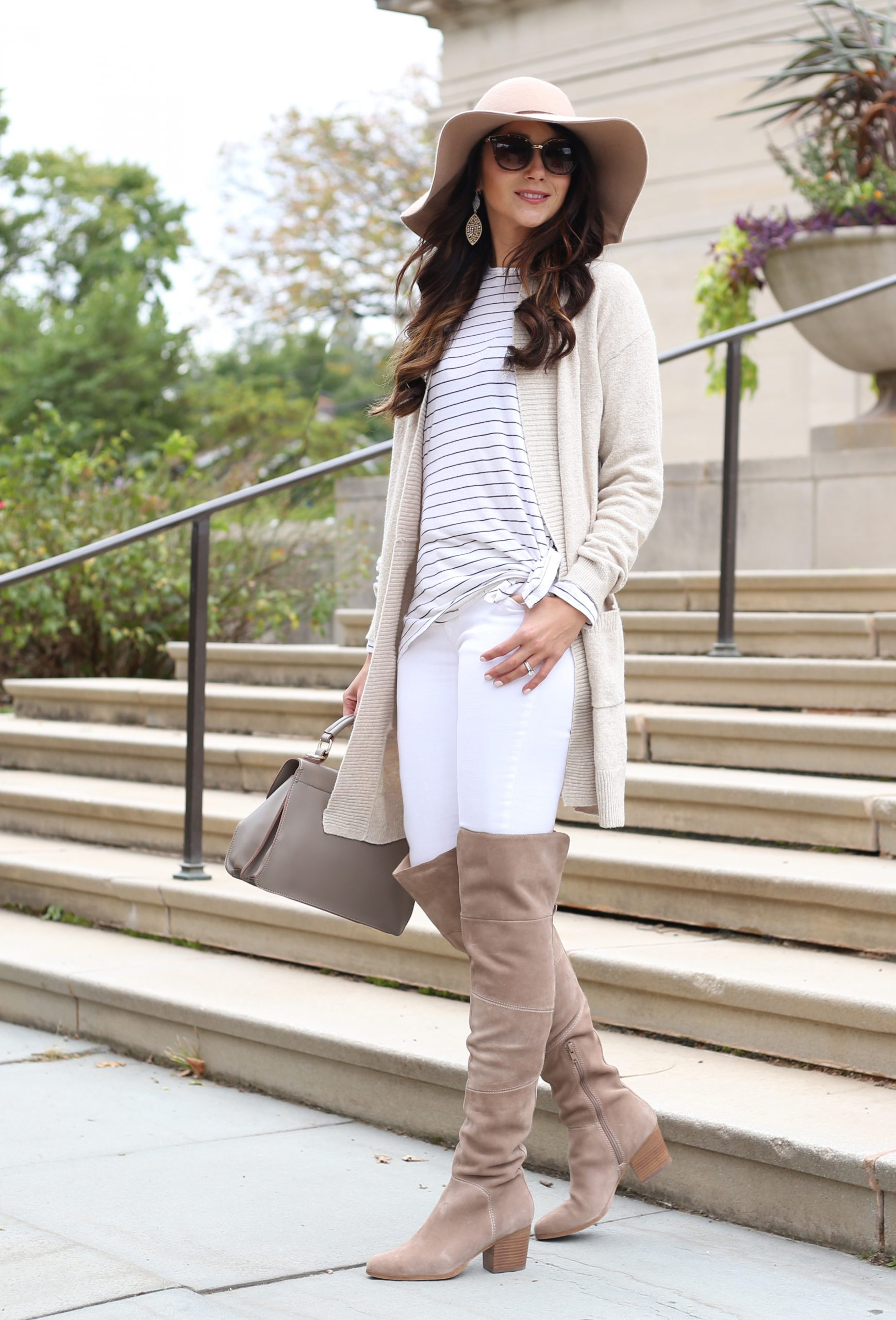 blogger Anna Monteiro of blushing rose style blog wearing cozy fall sweaters and cream color cardigan with striped tee and over the knee boots in this cute fall outfit with floppy hat