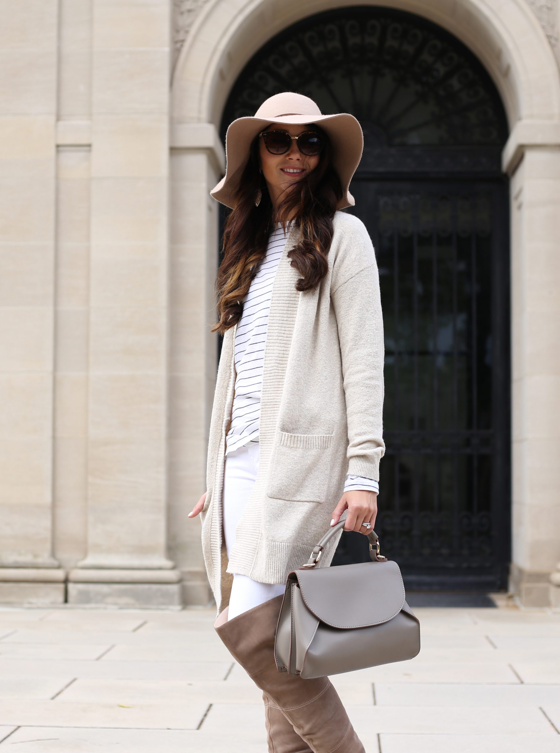blogger Anna Monteiro of Blushing Rose Style wearing cozy fall sweater with white skinny jeans and taupe over the knee boots cream cardigan and floppy hat in this cute fall outfit