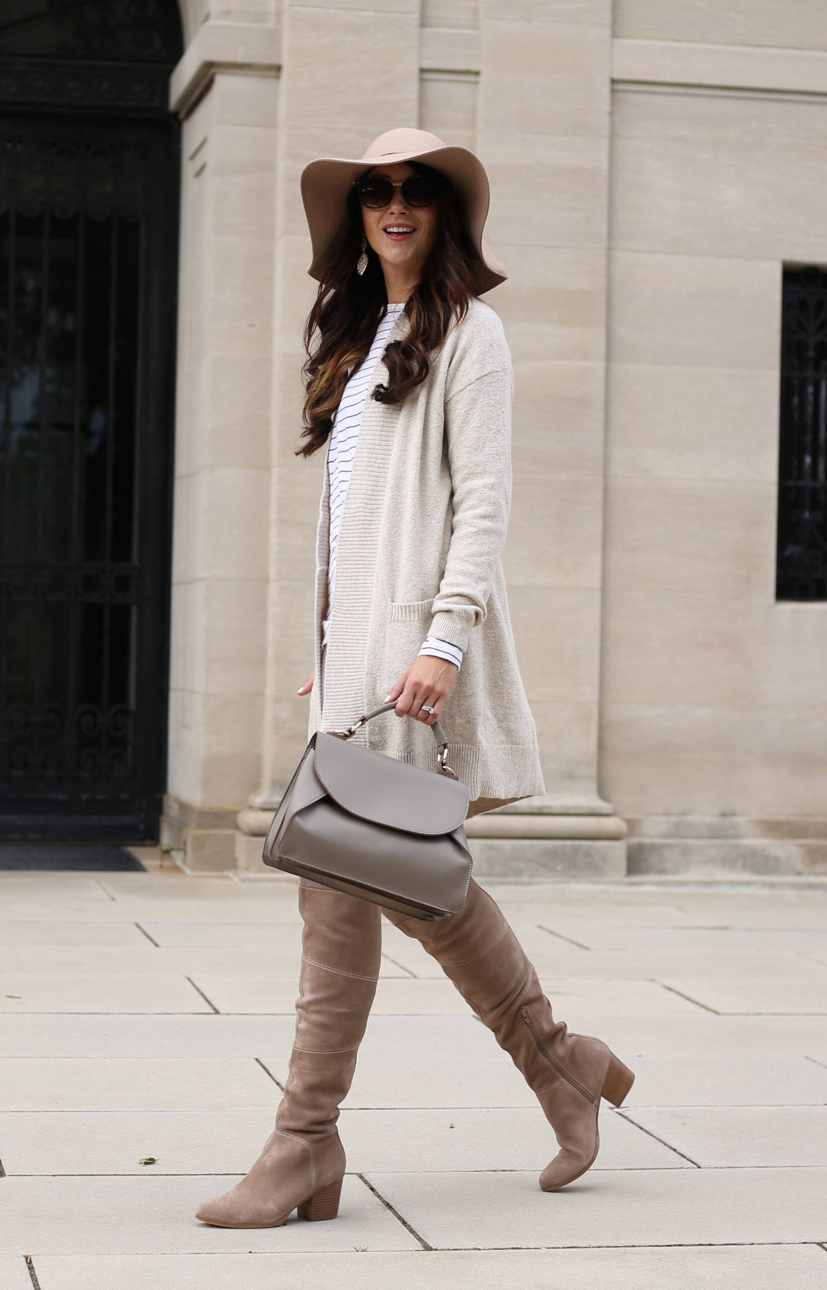 Anna Monteiro of Blushing ROse Style blog wearing cream color cardigan and white jeans with taupe over the knee boots in cozy fall sweaters and cute fall outfit
