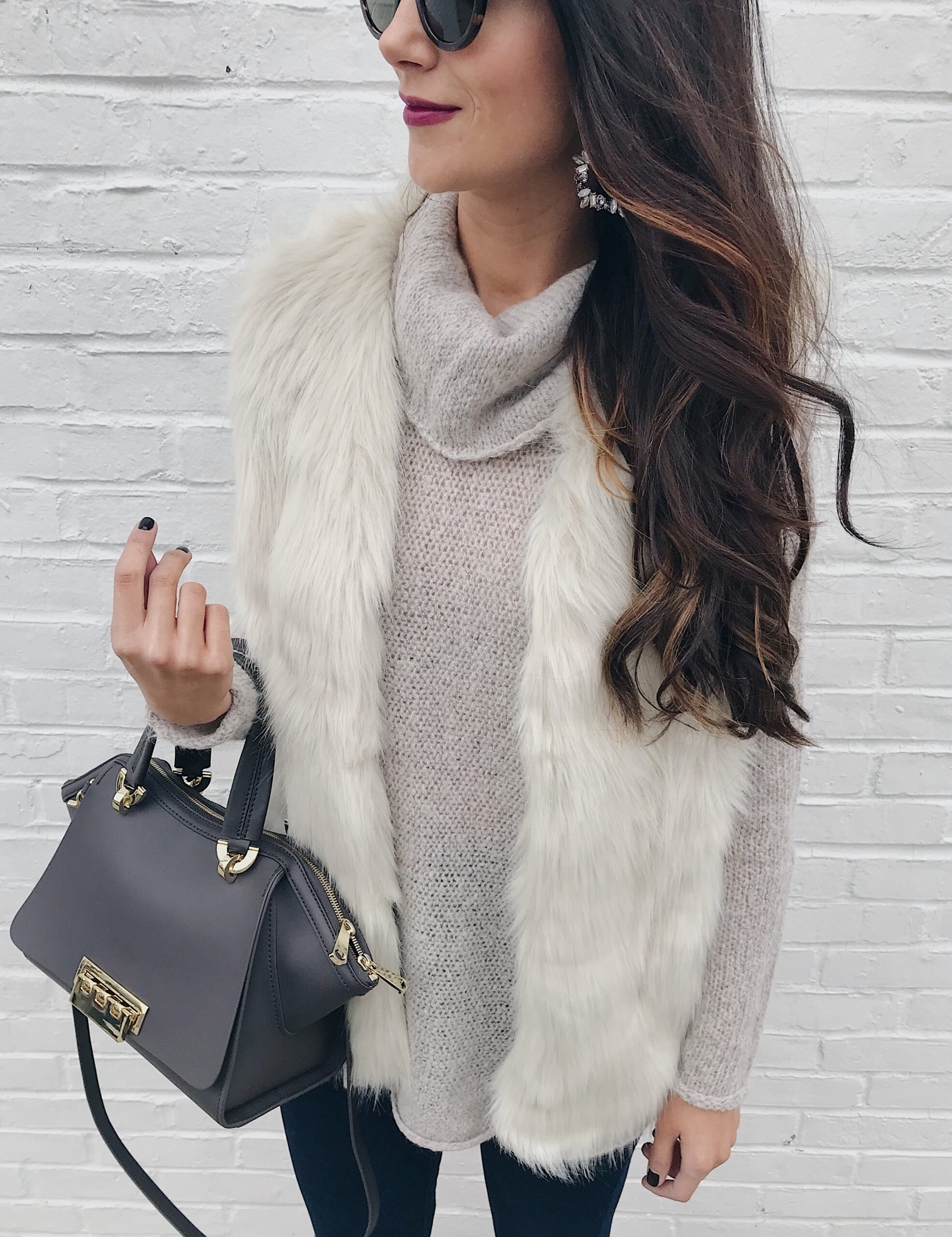 anna monteiro of blushing rose style blog wearing faux fur vest, and tunic sweater in 3 must have boot styles to own this season