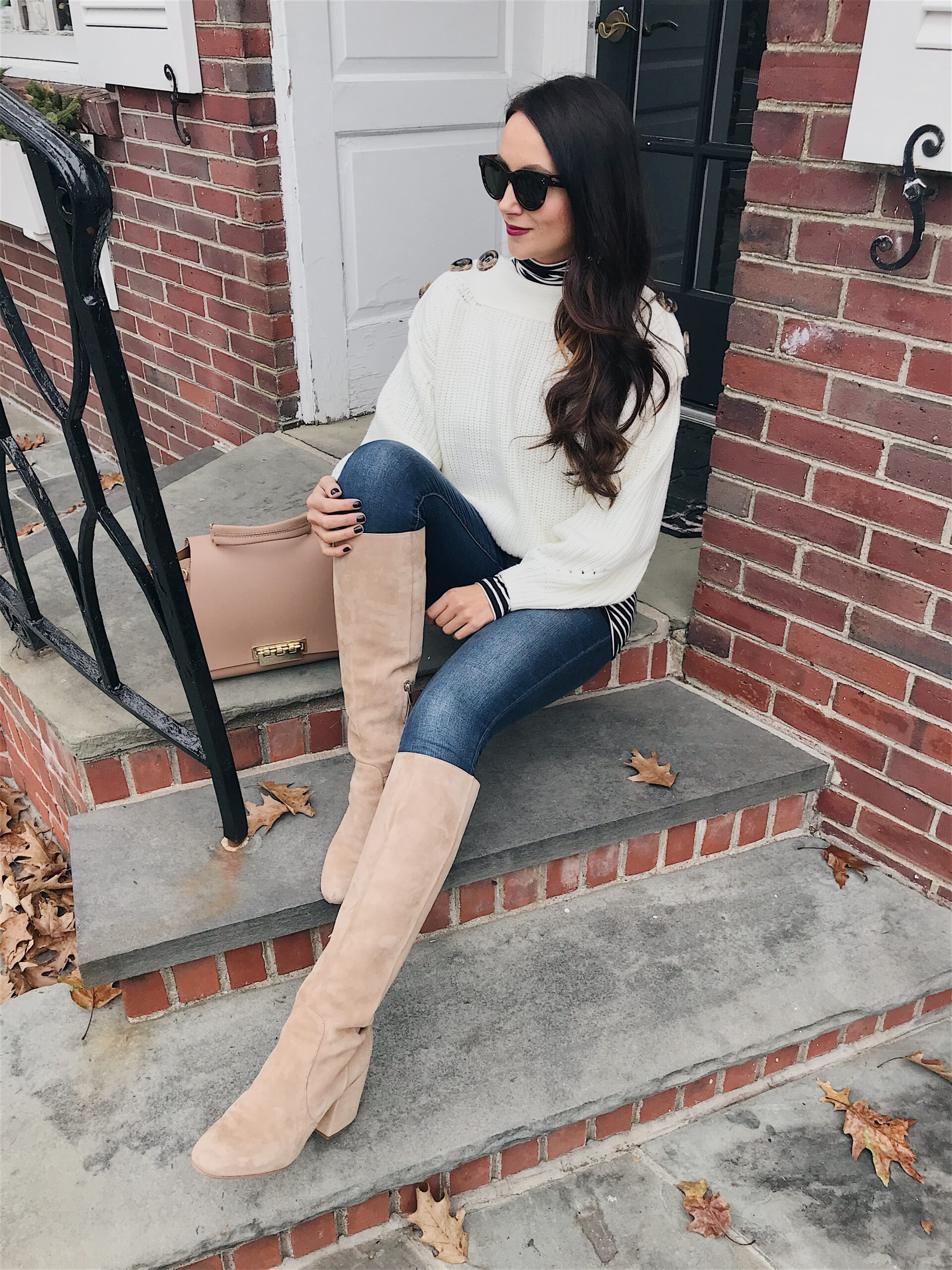 blogger anna monteiro of blushing rose style blog wearing cute winter outfit, striped turtleneck, knee high boots and beanie in 3 must have boot styles to own this season