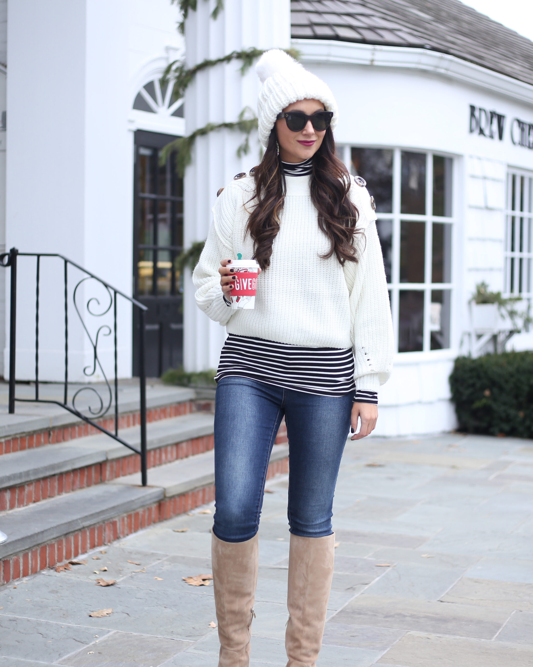 blogger Anna Monteiro wearing winter outfit with knee high boots and white sweater in 3 must have boot styles to own this season