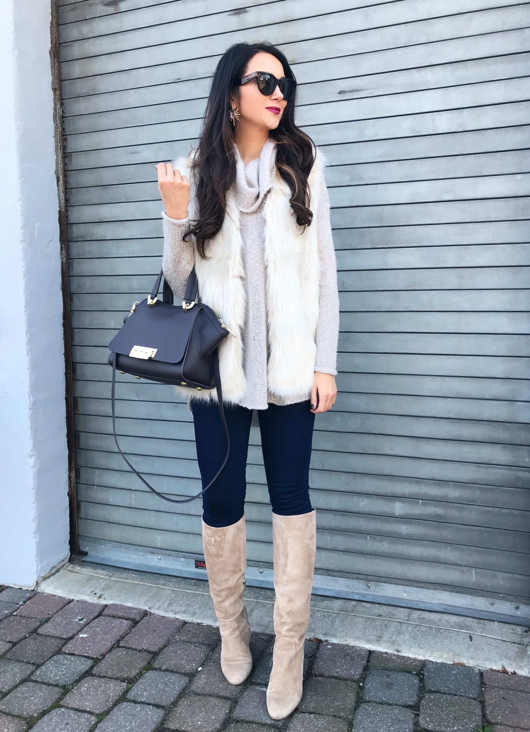 anna monteiro of blushing rose style wearing knee high boots and faux fur vest in 3 must have boot styles to own this season