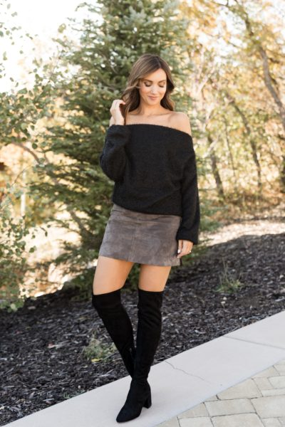 Off shoulder sweater paired with mini skit and OTK boots