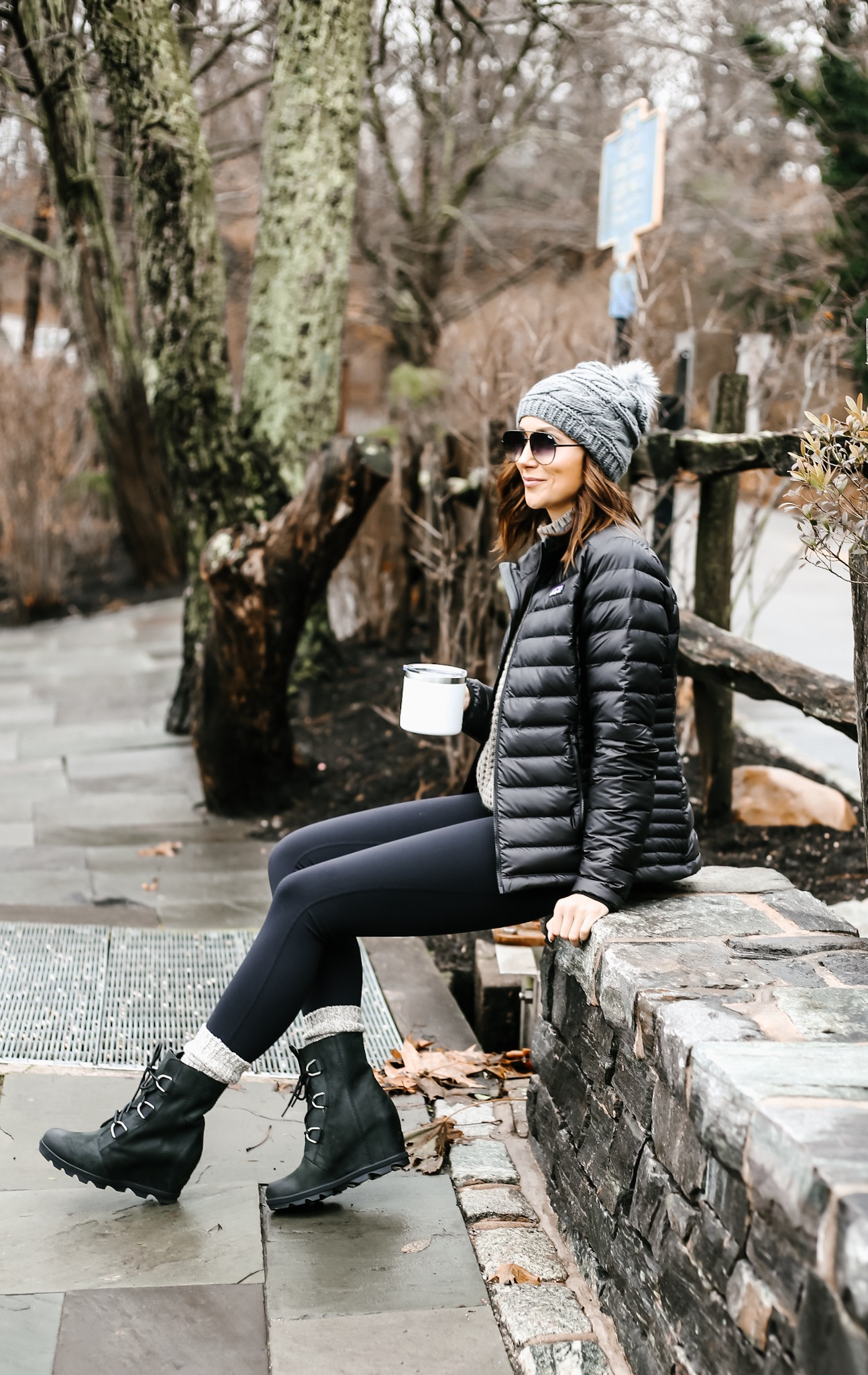 women sitting in the park, in warm leggings, sorel joan of arctic boots and patagonia jacket
