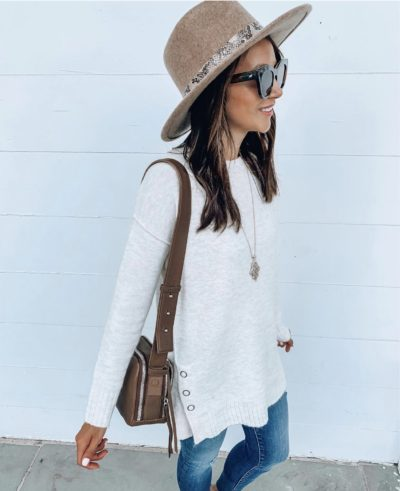 woman with hat and wearing tunic sweater and jeans