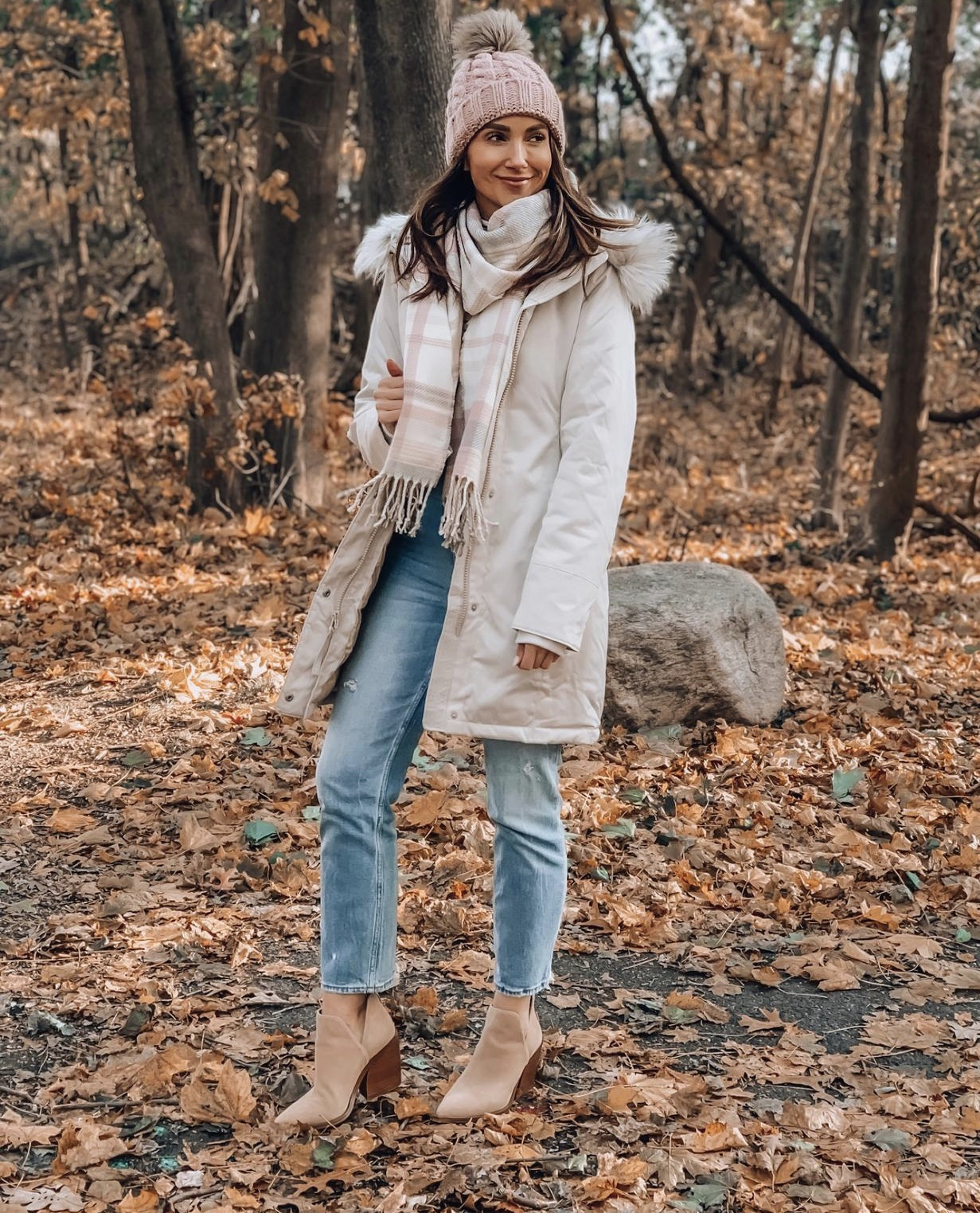 Woman wearing down jacket, jeans and booties