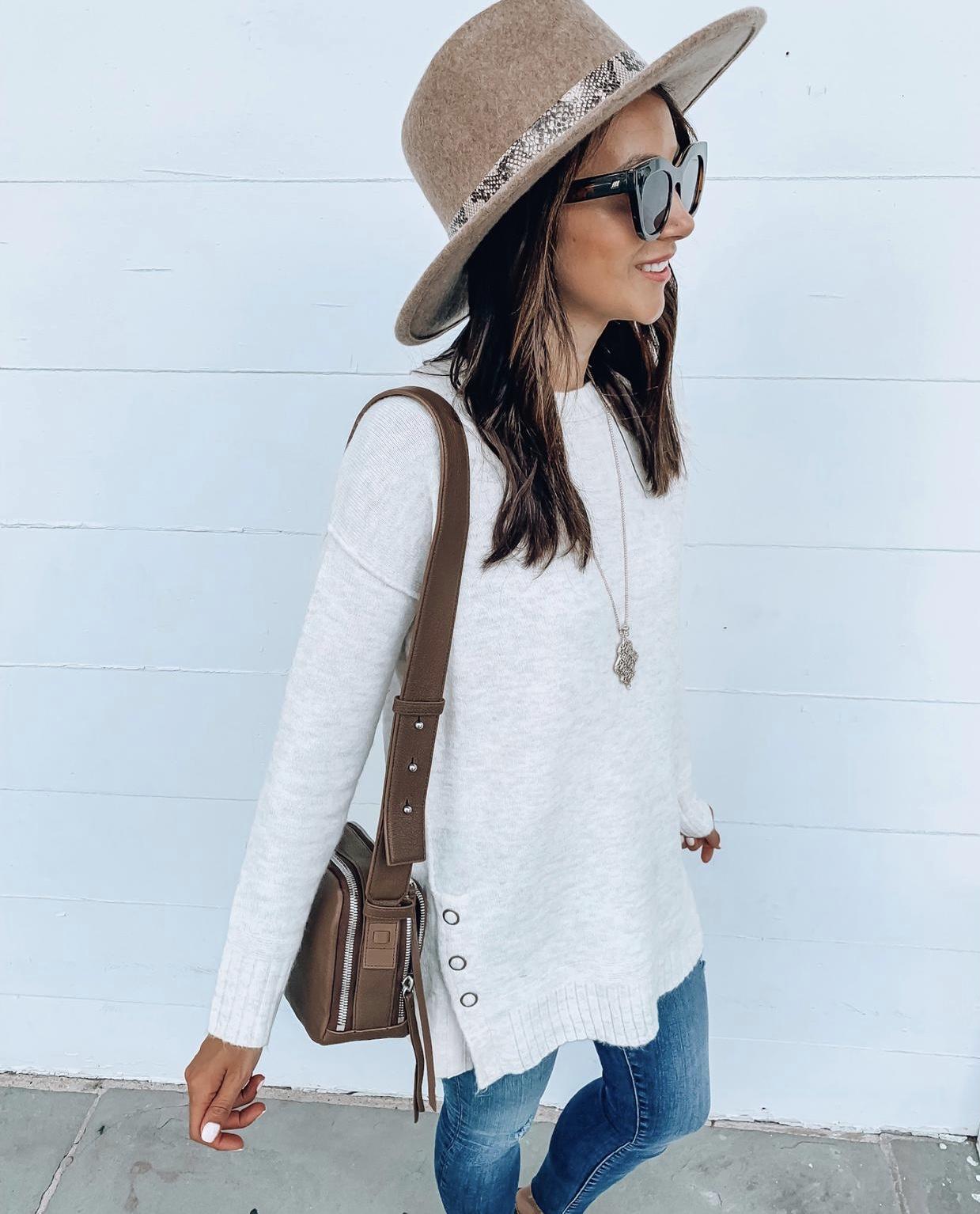 Woman wearing sweater tunic, hat, jeans